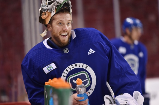 jacob-markstrom-enjoys-a-water-break-at-the-canucks-bench-during-practice
